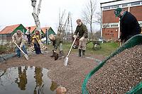 Grundschulklasse, Schulklasse legt einen Schulteich, Schul-Teich, Teich, Gartenteich, Garten-Teich im Schulgarten an, Kinder und Eltern verteilen feinkörnigen Kies im Teich, der als Bodensubstrat für den neuangelegten Teich dient