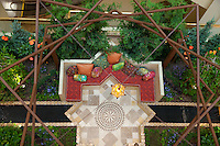 """A garden bench sits amid water features and lush foliage with a large wooden framework providing vertical detail.  The Orange Coast College Hotriculture Club entered the 2011 Spring Garden Show landscape design competition (http://www.springgardenshow.com/) and won first place in the student category for their """"Moorish Flourishes in a Contemporary Garden"""" design."""