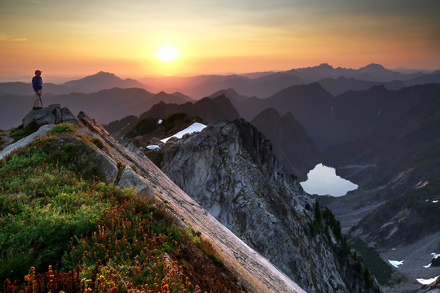 Climber on Vesper Peak at sunset with view of Copper Lake, Big Four Mountain, Little Chief Peak and other mountains, Central Cascade Mountains, Washington, USA