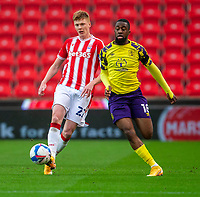 21st November 2020; Bet365 Stadium, Stoke, Staffordshire, England; English Football League Championship Football, Stoke City versus Huddersfield Town; Sam Clucas of Stoke City passes the ball away frpm Isaac Mbenza of Huddersfield Town