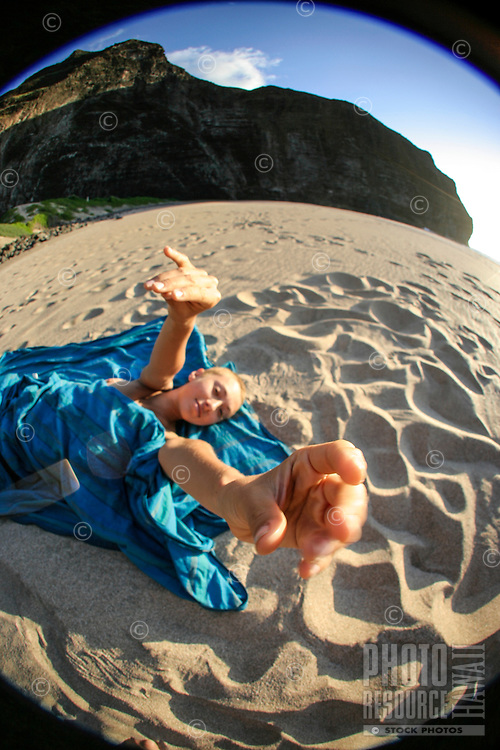 A young woman lying on a blue cloth with arms outstretched reaches up towards the camera at Honopu Beach, Na Pali Coast, Kaua'i.