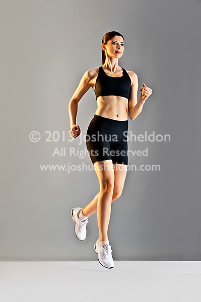 Young Caucasian woman running wearing black sports clothing