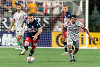 FOXBOROUGH, MA - JULY 7: Tommy McNamara #26 of New England Revolution brings the ball forward as Alejandron Pozuelo #10 of Toronto FC closes during a game between Toronto FC and New England Revolution at Gillette Stadium on July 7, 2021 in Foxborough, Massachusetts.