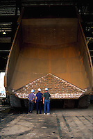 A huge, rusty ore truck with a tilted bed dwarfs the men standing in front of it.