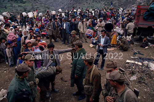 Isikveren, Turkey.April 15, 1991..Kurdish refugees are moved to smaller camps after passing through Turkish soldiers. They are moving a mountain top camp that housed an estimated  300,000 refugees that fled Iraqi's and Saddam Hussein's post Gulf war persecution...In the wake of the 1991 Persian Gulf War rebellions in Southern and Northern Iraq occurred. The uprising in the Kurdish areas of Northern Iraq broke out in March, sparked by demoralized Iraqi Army troops returning from it's defeat against United States lead coalition forces in southern Iraq and Kuwait. Although they presented a threat to Iraqi President Saddam Hussein?s regime, his Iraqi Republican Guard suppressed the rebellion with massive force, as the expected US intervention never materialized. ..The faltering rebellion fueled a terrified mass exodus. The U.N. High Commissioner for Refugees called it the largest in its 40?year history. During March and early April, nearly two million of Iraqis escaped from strife-torn cities to the mountains along the northern borders and into Turkey and Iran. Their exodus was sudden and chaotic, with thousands fleeing on foot, on donkeys, or crammed onto open-backed trucks and tractors. Thousands, many of them children, died or suffered injury along the way, primarily from adverse weather, unhygienic conditions and insufficient food and medical care. Some were killed by army helicopters, which deliberately strafed columns of fleeing civilians. Others were injured when they stepped on land mines planted by Iraqi troops near the Iran border during the war. Greenpeace has estimated that at one point in 1991, an estimated 2,000 Kurds were dying every day..