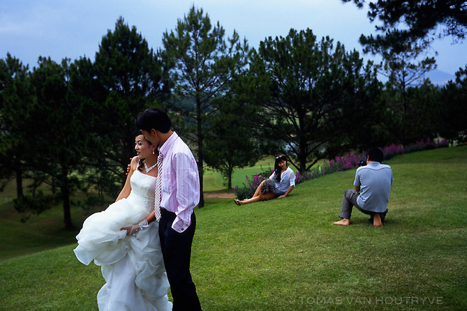 A newly married couple embraces while a photographer poses his assistant on the golf course in Dalat, Vietnam on 5 March 2010.