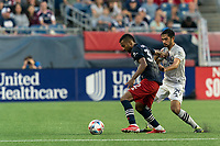 FOXBOROUGH, MA - JULY 25: Christian Mafla #32 of New England Revolution dribbles as Mathieu Choiniere #29 of CF Montreal defends during a game between CF Montreal and New England Revolution at Gillette Stadium on July 25, 2021 in Foxborough, Massachusetts.