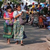 Antigua, Guatemala.  Two Young Maya Women in Traditional Clothing  Selling Necklaces in the Plaza de Armas.  Semana Santa.