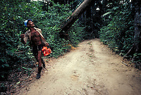 A worker with a chain saw walks on a dirt road in the rain forest, looking for hardwoods to harvest before the Tucurui dam floods the area. Logging. occupations, natural resources, trades. Para Brazil.
