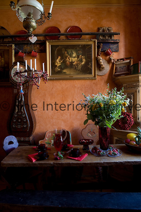 Bowls of fruit, fresh flowers and red glassware laid out on the rustic table in the kitchen