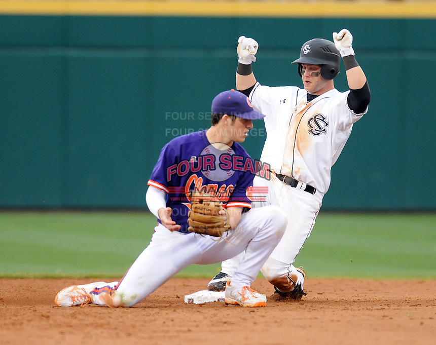First baseman Christian Walker (13) of the South Carolina Gamecocks slides safely into second base with a double in a game against the Clemson Tigers on March 3, 2012, at Carolina Stadium in Columbia, South Carolina. Defending is Clemson second baseman Steve Wilkerson (17). South Carolina won, 9-6. (Tom Priddy/Four Seam Images)