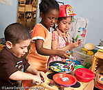 Education preschool 3-4 year olds boya nd two girls playing in kitchen family area pretend play with cooking and dishes