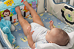 5 month old baby boy in crib on back using feet to hit sound and action board
