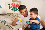 Three year old boy playing with toy vehicles and father