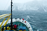 A figure on the bow of the Arctic expedition ship, Akademik Shokakskiy, works hard to set the anchor during a winter storm. The ship was forced to take shelter in a bay during the storm off Baffin Island, Nunavut, Canada.