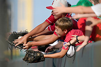 Fans of the Greenville Drive reach out for a ball held by Cole Brannen in a game against the Hickory Crawdads on Sunday, August 29, 2021, at Fluor Field at the West End in Greenville, South Carolina. (Tom Priddy/Four Seam Images)