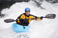 Heather Armitage paddles through a hole in a whitewater kayak on the Kananaskis River, Kananaskis County, Alberta, Canada
