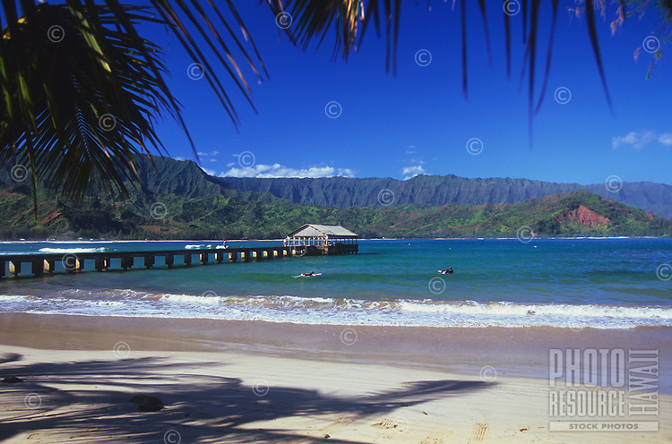 People stroll on Hanalei Pier and paddle out to surf in the waters of Hanalei Bay on the north shore of Kaua'i.