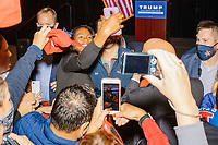 People pose for pictures with a giant American flag after Donald Trump, Jr., the son of US president Donald Trump, spoke at a 'Make America Great Again!' campaign rally at DoubleTree by Hilton MHT in Manchester, New Hampshire, on Thu., Oct. 29, 2020. The event took place five days before the Nov. 3 presidential election. The woman in the center posing with Donald Trump, Jr., is Rayla Campbell, a write-in Republican candidate running to unseat Massachusetts Representative Ayanna Pressley.