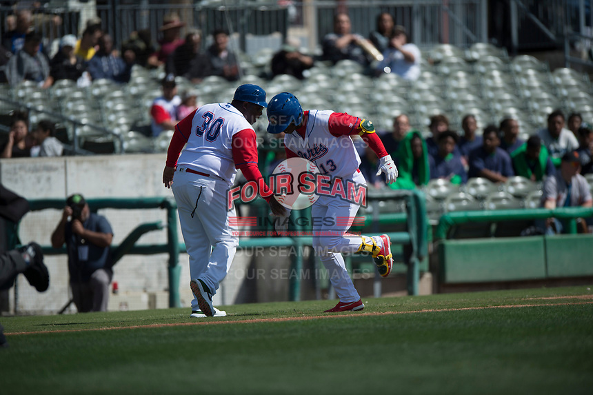 Stockton Ports left fielder Lazaro Armenteros (13) is congratulated by manager Webster Garrison (30) after hitting a home run during a California League game against the San Jose Giants on April 9, 2019 in Stockton, California. San Jose defeated Stockton 4-3. (Zachary Lucy/Four Seam Images)