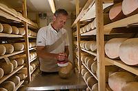 France, Pas-de-Calais (62), Wierre-Effroy :  Fromagerie: La Ferme du Vert   Antoine Bernard  surveille l'affinage de ses mimolettes au lait cru AUTO N: 2013-135// France, Pas de Calais,  Wierre Effroy: cheese: La Ferme du Vert, Antoine Bernard monitors refining its mimolettes raw milk