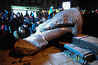 Protesters vandalize the remainigs of the fallen statue of Lenin in Kiev