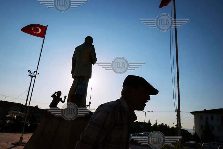A man walking in a square while children play near by a statue of Mustafa Kemal Ataturk.