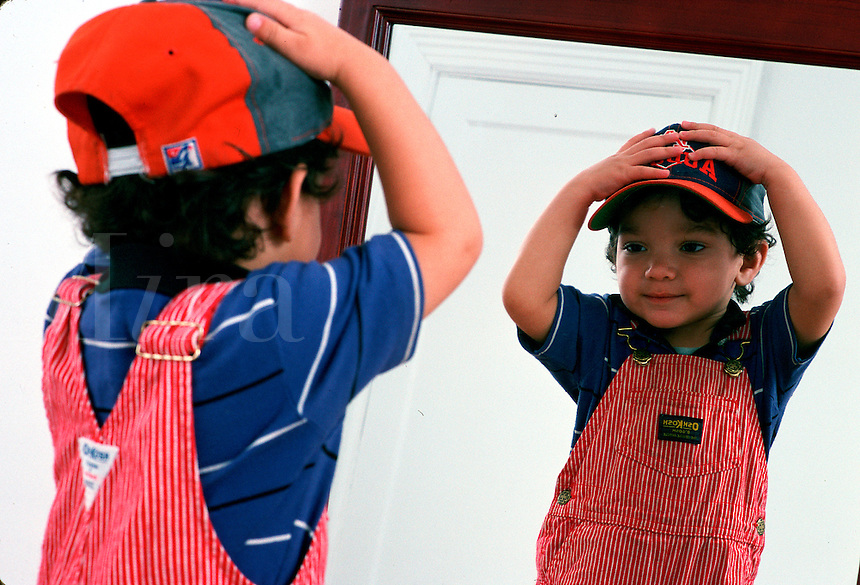 Toddler is fascinated, dressing himself in a hat and playing with his image in a mirror.