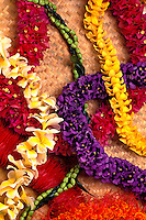 An assortment of beautiful floral leis are arranged  on a woven lauhala mat.