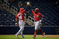 Washington Nationals Josh Harrison (5) high fives Yadiel Hernandez (29) after hitting a home run during a Major League Spring Training game against the Houston Astros on March 19, 2021 at The Ballpark of the Palm Beaches in Palm Beach, Florida.  (Mike Janes/Four Seam Images)