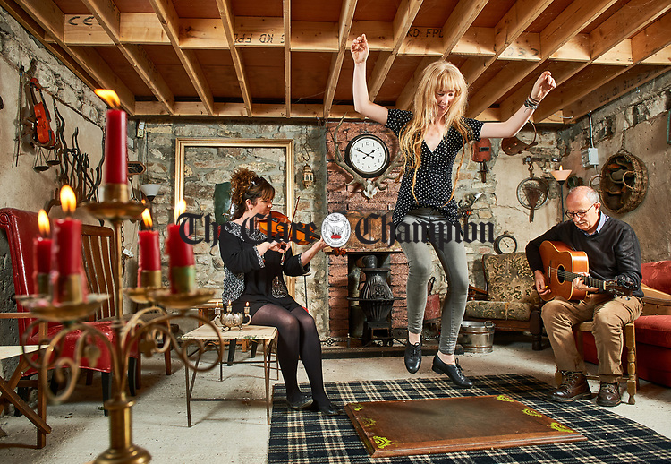 "Cliodhna Donnellan, co-ordinator of The Mountshannon Trad Festival, at left, and Terence O Reilly, play for dancer Stephanie Keane in the new festival venue ""The Store"" ahead of the forthcoming Mountshannon Trad Festival which is on 28th to 30th September. Stephanie and Terence will be giving workshops, as part of the weekend, on sean Nos dancing and trad guitar. Photograph by John Kelly."