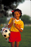 smiling young girl carrying soccer balls