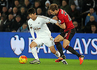 L-R Ki Sung Yueng of Swansea against Craig Dawson of West Bromwich Albion during the Barclays Premier League match between Swansea City and West Bromwich Albion played at the Liberty Stadium, Swansea on December 26 2015