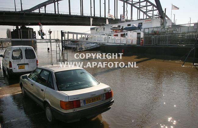 Arnhem 130306 ondanks dat de temperatuur nog niet echt meewerkt, is de lente op komst , de sneeuw in duitsland en zwitserland smelt en de rijnkade in Arnhem loopt onder water.<br />De schepen hebben hun loopbruggen verlengt en de deze beide auto's moeten snel wegwezen.<br />Foto frans ypma APA-foto