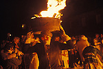 Allendale Tar Barrel Parade. Allendale Northumberland. Uk. 1972. New Years Eve. Fire Festival. Guisers walk around the small town with burning half tar barrels on thier heads and at midnight place them on a huge bonfire in the centre of town.