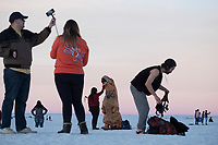 People, including one dressed as a dinosaur, look at the sunset from atop dunes at White Sands National Monument near Alamogordo, New Mexico, USA, on Sat., Dec. 30, 2017.