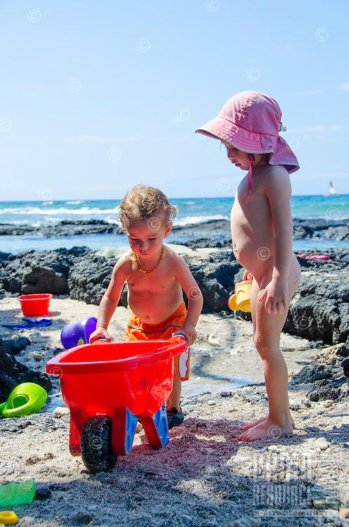 A local boy and girl play at a beach in Puako, South Kohala, Hawai'i Island.