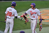 Third baseman Adam Renwick (11) of the Clemson University Tigers is congratulated by Seth Beer (28) after scoring a run in a game against the Wofford College Terriers on Tuesday, March 1, 2016, at Doug Kingsmore Stadium in Clemson, South Carolina. Clemson won, 7-0. (Tom Priddy/Four Seam Images)