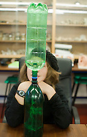 A student watches water drain from the upper bottle to the lower one and create a vortex as it goes (Coriolis effect), Summerhill School, Leiston, Suffolk. The school was founded by A.S.Neill in 1921 and is run on democratic lines with each person, adult or child, having an equal say.  You don't have to go to lessons if you don't want to but could play all day.  It gets above average GCSE exam results.