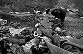 Grozny, Chechyna.1995.A man finds one of his two dead sons amongst the hundreds of corpses in an open mass grave. He is able to identify the body by the clothing as the face has been eaten away by street dogs.