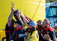 Nov 17, 2019; Pomona, CA, USA; Crew members for NHRA pro stock driver Erica Enders celebrate with the trophy after clinching the 2019 top fuel world championship during the Auto Club Finals at Auto Club Raceway at Pomona. Mandatory Credit: Mark J. Rebilas-USA TODAY Sports