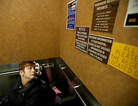 Kara reads prison-like restrictions posted in the elevator of a nursing home that she is working get a client out of. Photo by James R. Evans©
