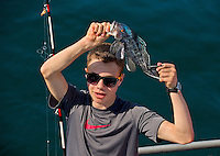 A Boy Scout shows off his ocean catch caught while deep-sea fishing about 15 miles off the South Carolina coast near Huntington Beach State Park. Image is model released.