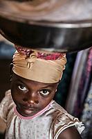 Mercato di Cotonou, banchi, Ritratto di bambina di colore che trasporta un contenitore sulla testa