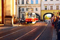 A picture of tram coming to a stop on Prague street. Crowd of people (tourists) are waiting for a tram in Prague, Czech Republic.