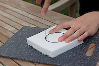 Mädchen, Kind bastelt eine Becherlupe, Beobachtungsgefäß aus 2 durchsichtigen Plastikbecher, einem Stück Styropor und Frischhaltefolie. 2. Schritt: Bechergroßer Kreis wird aus Styroprplatte ausgeschnitten