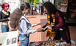 WATERBURY, CT 073021JS01 Magician Michael OJ performs a card truck with Zhaynah James, 14 in front of John Bale Bookstore during Harry Potter Day festivities in downtown Waterbury on Friday. <br />  Jim Shannon Republican American