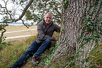 BNPS.co.uk (01202) 558833. <br /> Pic: CorinMesser/BNPS<br /> <br /> Pictured: John Challinor, chairman of the Parkstone Bay Residents Association, with one of the oak trees which had four holes drilled through its trunk. <br /> <br /> Police have launched an investigation into allegations a wealthy homeowner has killed two 'magnificent' oak trees because they blocked their sea views.<br /> <br /> The 70ft tall mature specimens have had holes drilled into their trunks and poison poured inside in a 'disgraceful' act of sabotage. <br /> <br /> The two trees stand on the edge of a recreation ground between Poole Harbour, Dorset, and a cluster of luxury homes that sell for between £2m to £3m.