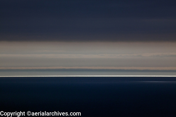 aerial photograph of light reflection on the Pacific ocean at the horizon beyoned a layer of fog Ventura County, California