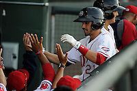 Second baseman Carlos Asuaje (20) of the Greenville Drive is congratulated after scoring a run in a game against the Augusta GreenJackets on Thursday, July 10, 2014, at Fluor Field at the West End in Greenville, South Carolina. Augusta won, 8-2. (Tom Priddy/Four Seam Images)
